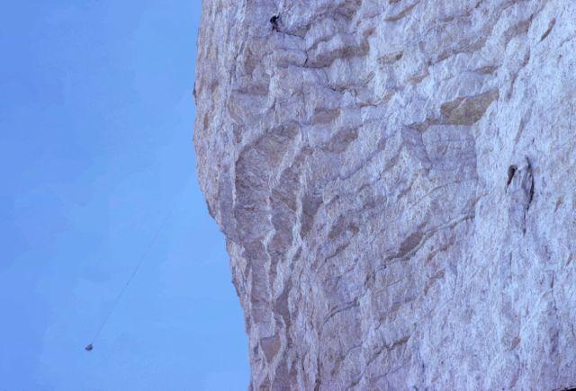 Schweizer Weg an der Nordwand der Westlichen Zinne (Dolomiten), 1961, ich oben, mein Spezl Willi Pecher unten rechts (im darauffolgenden Winter in einer Lawine umgekommen), links unten der Rucksack, der aufgrund des 40 m weit ausladenden Dachüberhangs beim Aufziehen (ein Biwak) derart weit aus der Wand gependelt ist, aufgenommen von Anneliese Degner vom Wandfuß (sie lebt wahrscheinlich nicht mehr, war zehn Jahre älter als ich).